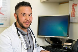 A transmasculine doctor with his compute