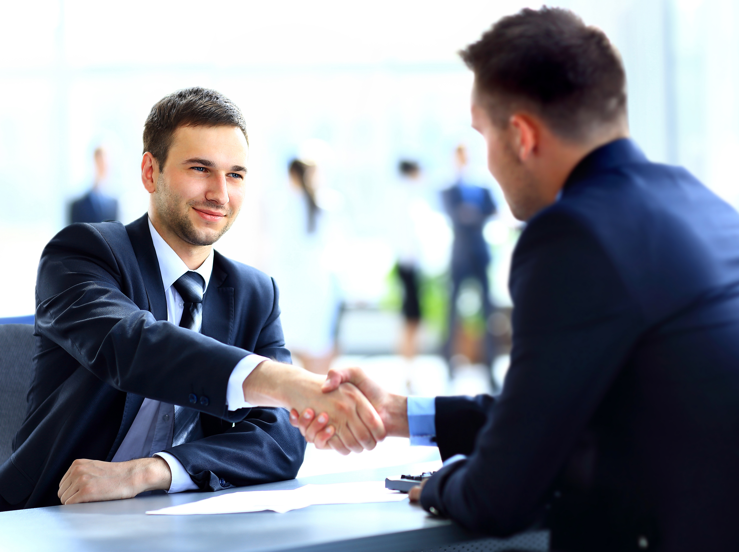 Two business colleagues shaking hands during meeting.jpg