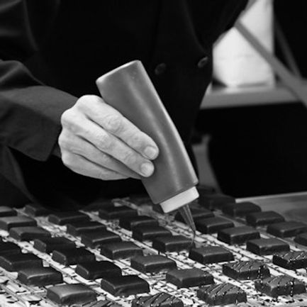 Chocolatier decorating caramels