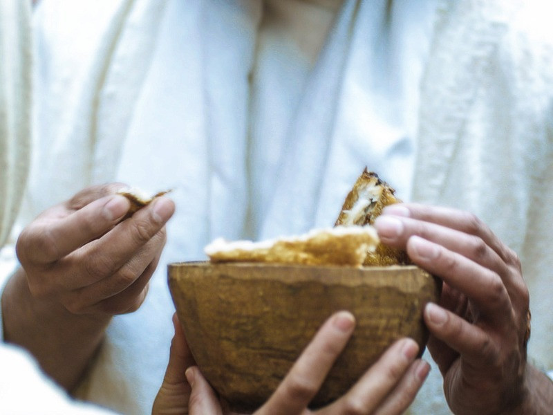 Bowl of bread and fish being shared by Jesus and the Disciples