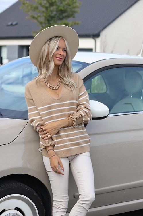 Pull beige rayé blanc.  Le col V apporte beaucoup de féminité à ce pull. Détails à froufrou au niveau des manches.