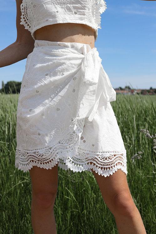 Jupe portefeuille blanche broderies.  Superbes détails de dentelles au bas de la jupe.  Idéale pour la chaude saison