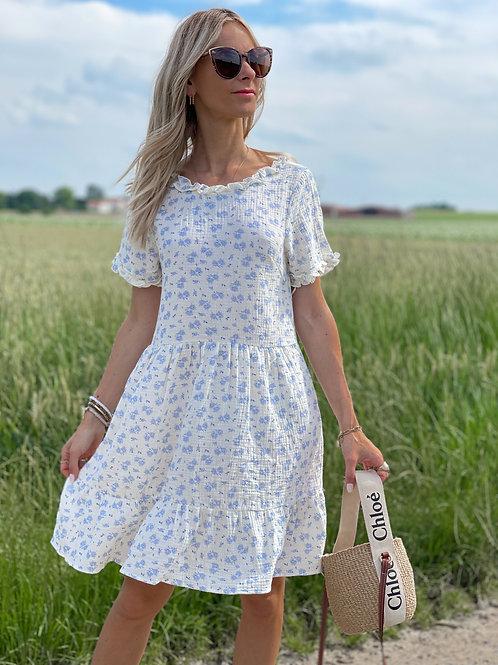 Robe blanche avec des fleurs bleues.  Très beau décolleté en rond dans le dos.