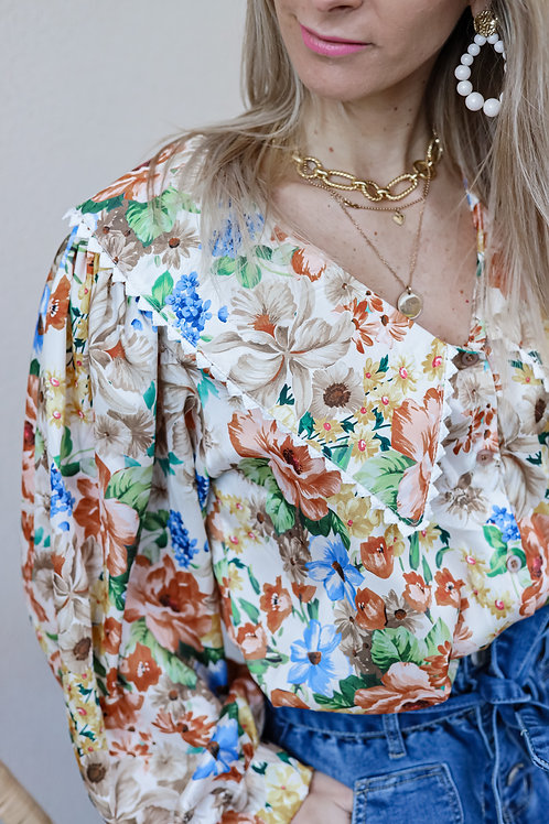 Chemise avec col descendant , motif fleuri coloré . Ce modèle est très Printanier ! Fabriquée en Italie.