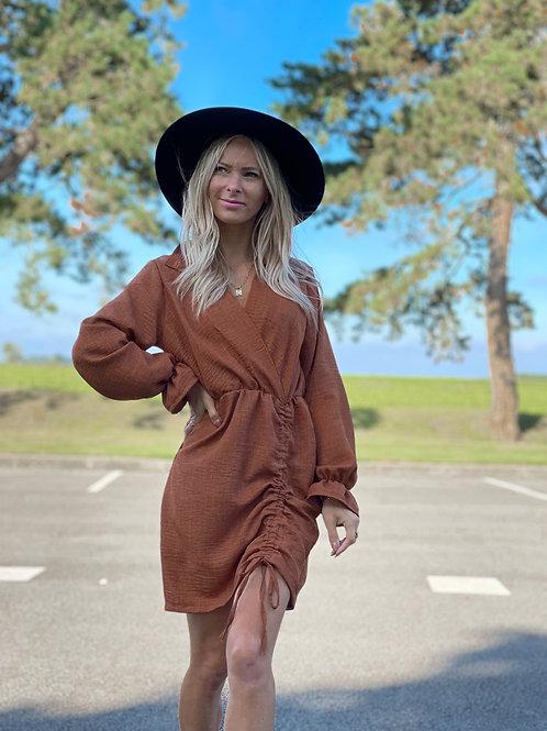 Robe de couleur camel qui se règle grâce à un lacet.