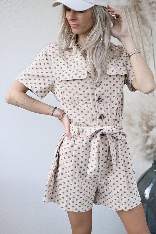 Combishort en matière jean , beige effet léopard. Elle possède des poches à l'avant , ainsi qu'une ceinture.  100% coton