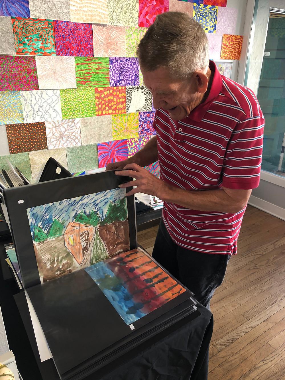 Artist John Houston looking through his portfolio of work in Santa Barbara Art Works front gallery.