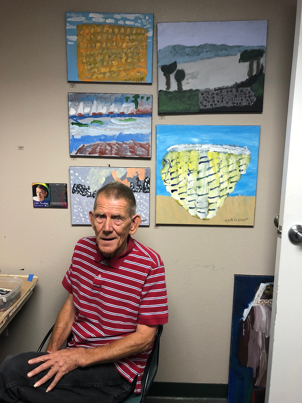 John Houston in his studio with five acrylic paintings behind him