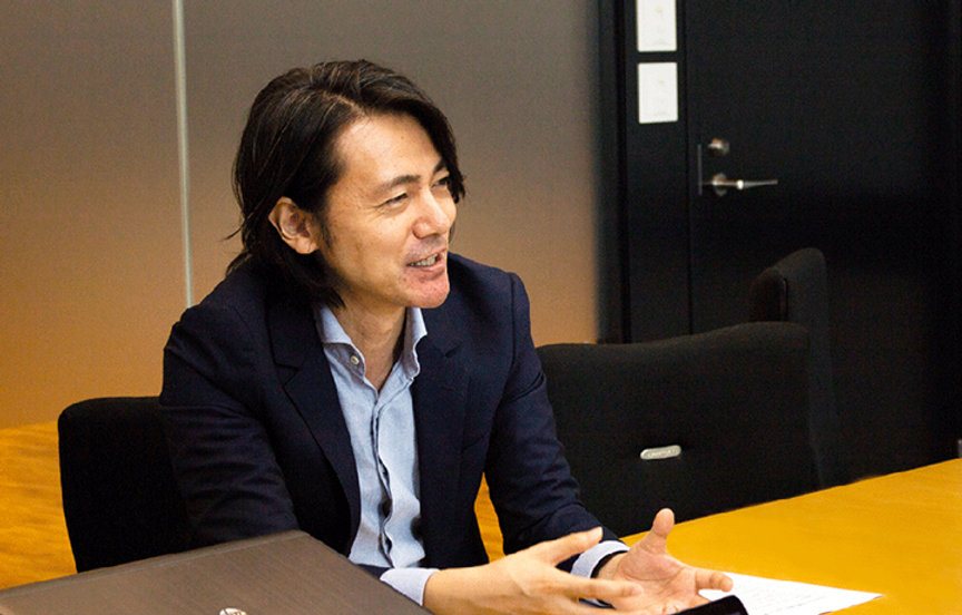 写真:手振りを交えて笑顔でお話する本間氏