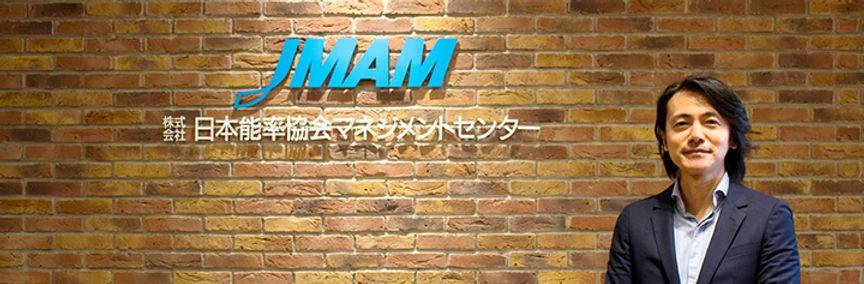写真:JMAM(日本能率協会マネジメントセンター)のロゴの前に立った本間氏