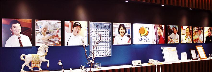 写真:すかいらーくの受付。ロゴマークと笑顔で働く社員のパネルが並んでいる。