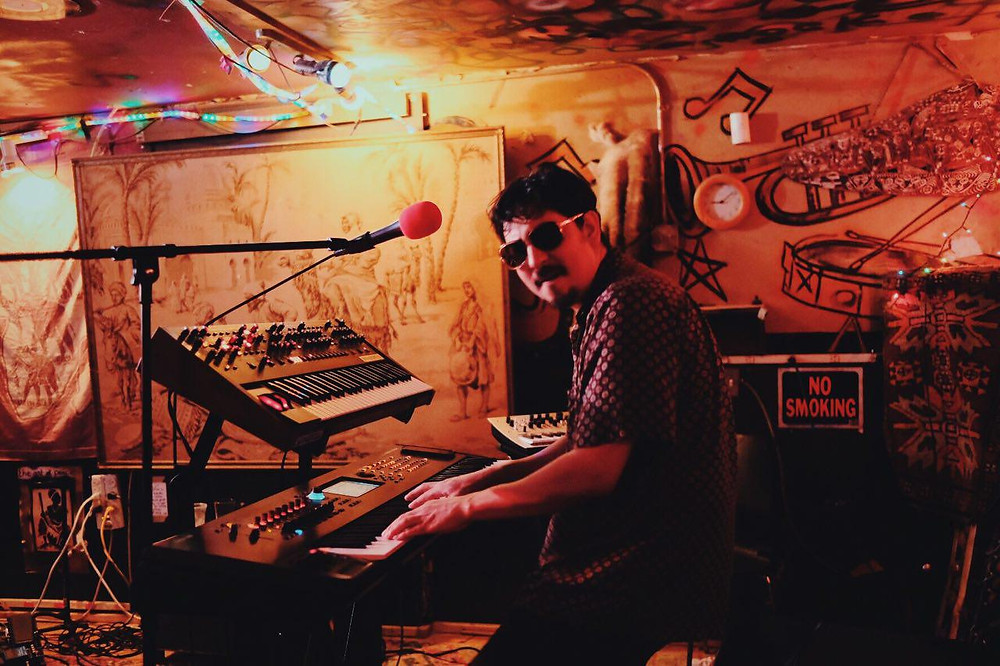 Man rocks the synth inside a dive bar.