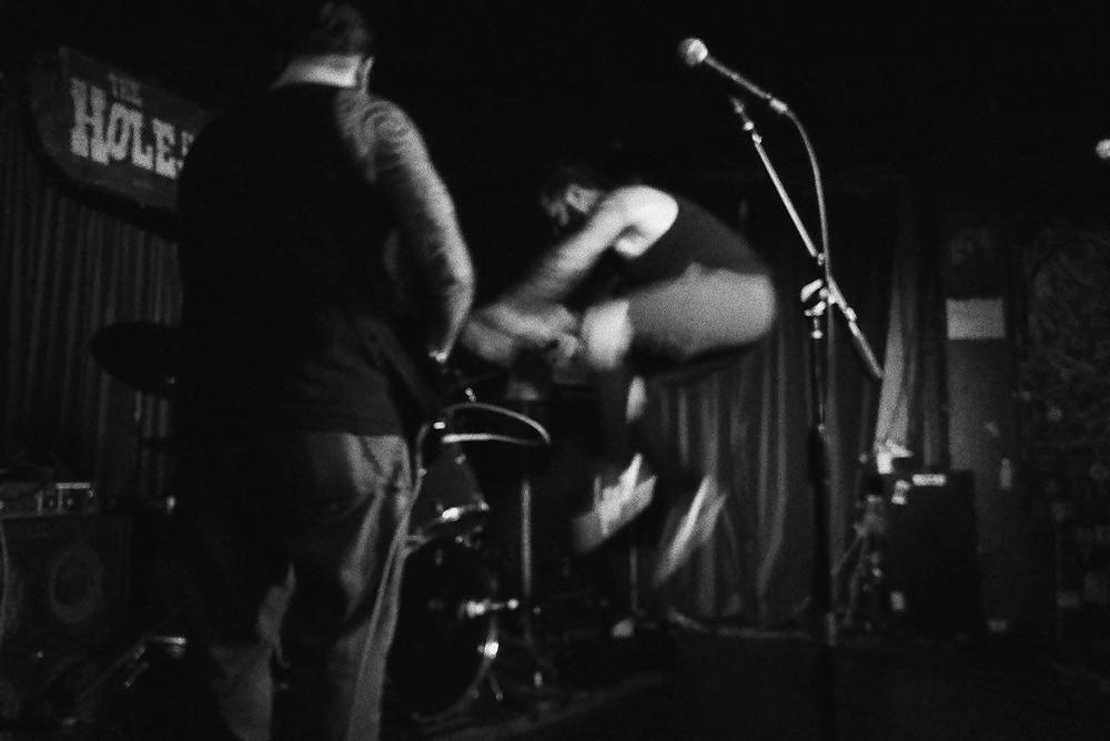 Man jumping on stage at dive bar.