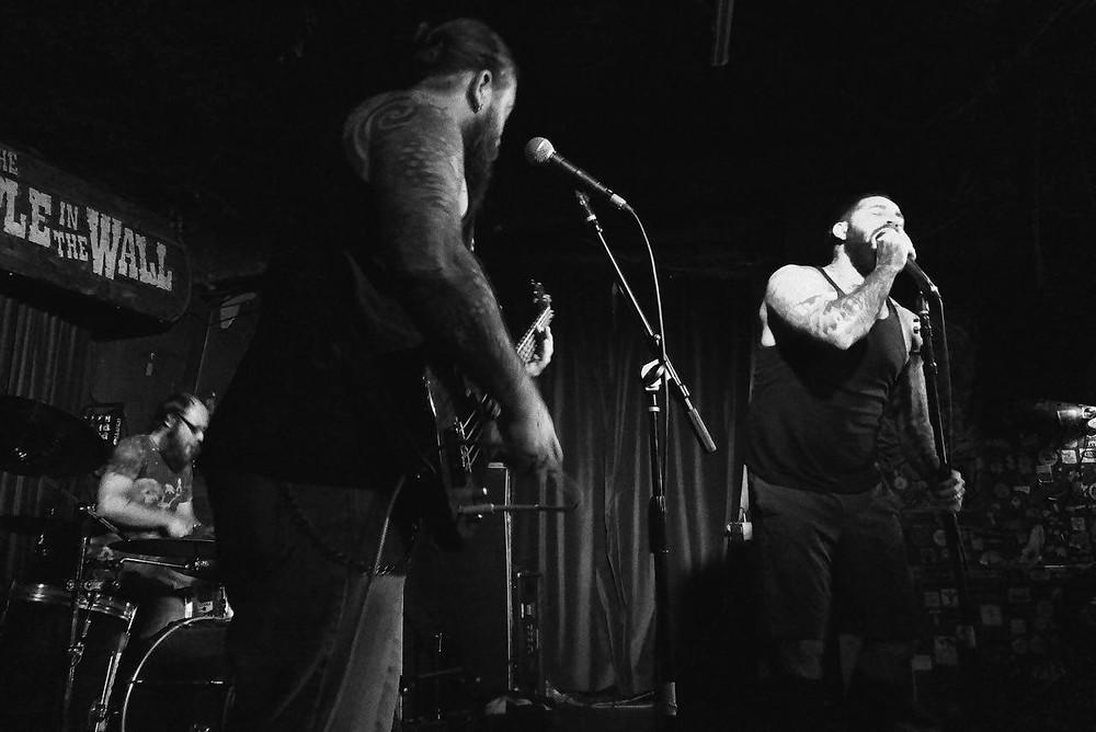 Man singing at hard rock dive bar.