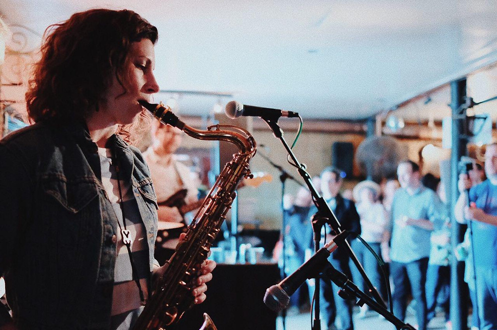 Woman plays the sax in a dive bar.