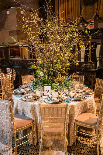 A tall arrangmenet consistig of blooming branches, cut Orchids and Tropcial green leavs for the Lenox Hill Gala at the Plaza.