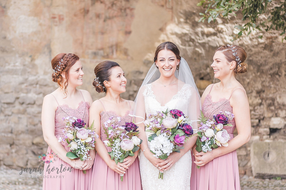bridesmaids group photo against italian castle walls in malcesine