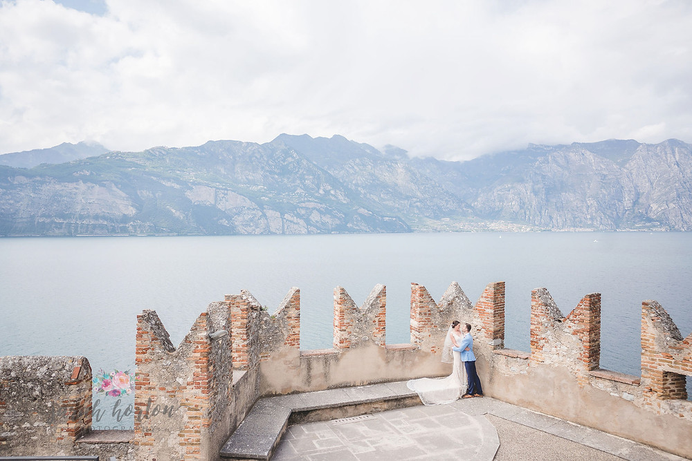 bride and groom against lake garda from malcesine castle rooftop