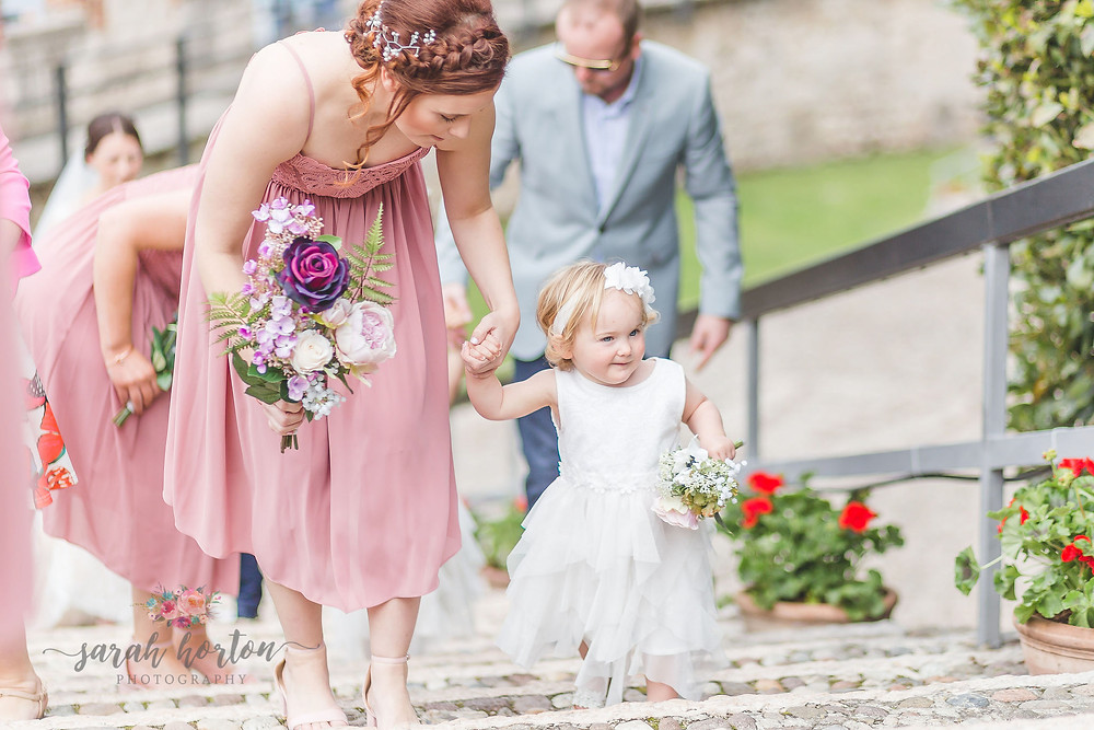 bridesmaid walks up castle steps with flower girl