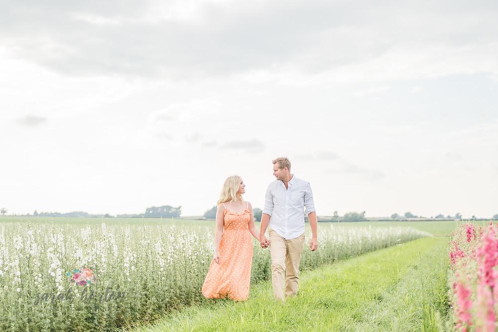 couple walk through white delphiniums at Shropshire petals confetti fields