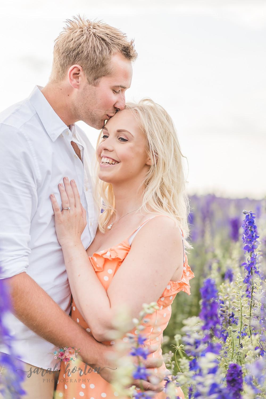 couple walk through purple delphiniums at Shropshire petals confetti fields