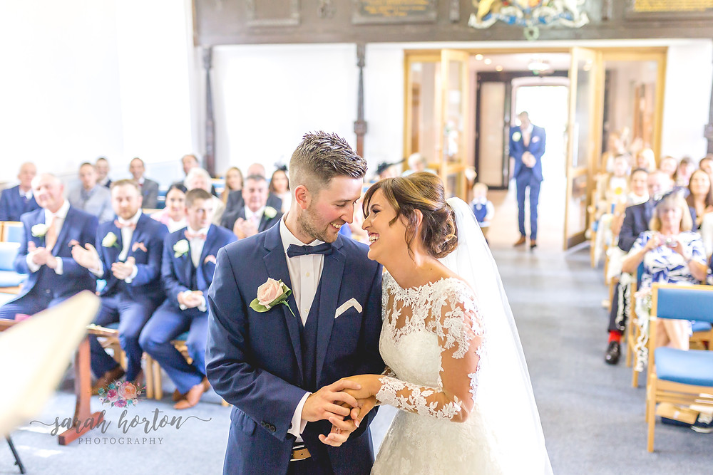 couple laugh in wedding photograph at chester church