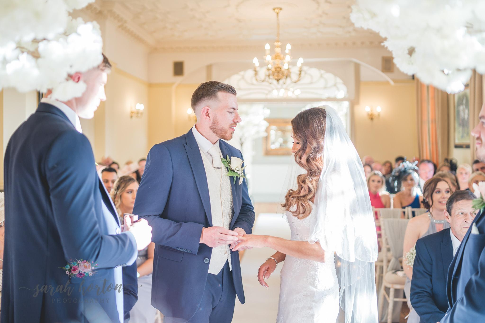 Groom puts ring onto brides finger at Nunsmere Hall