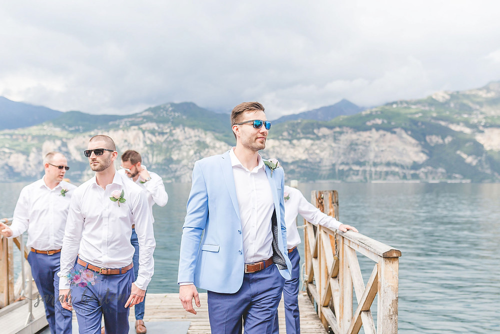 groom walks off jetty on lake garda with groomsmen