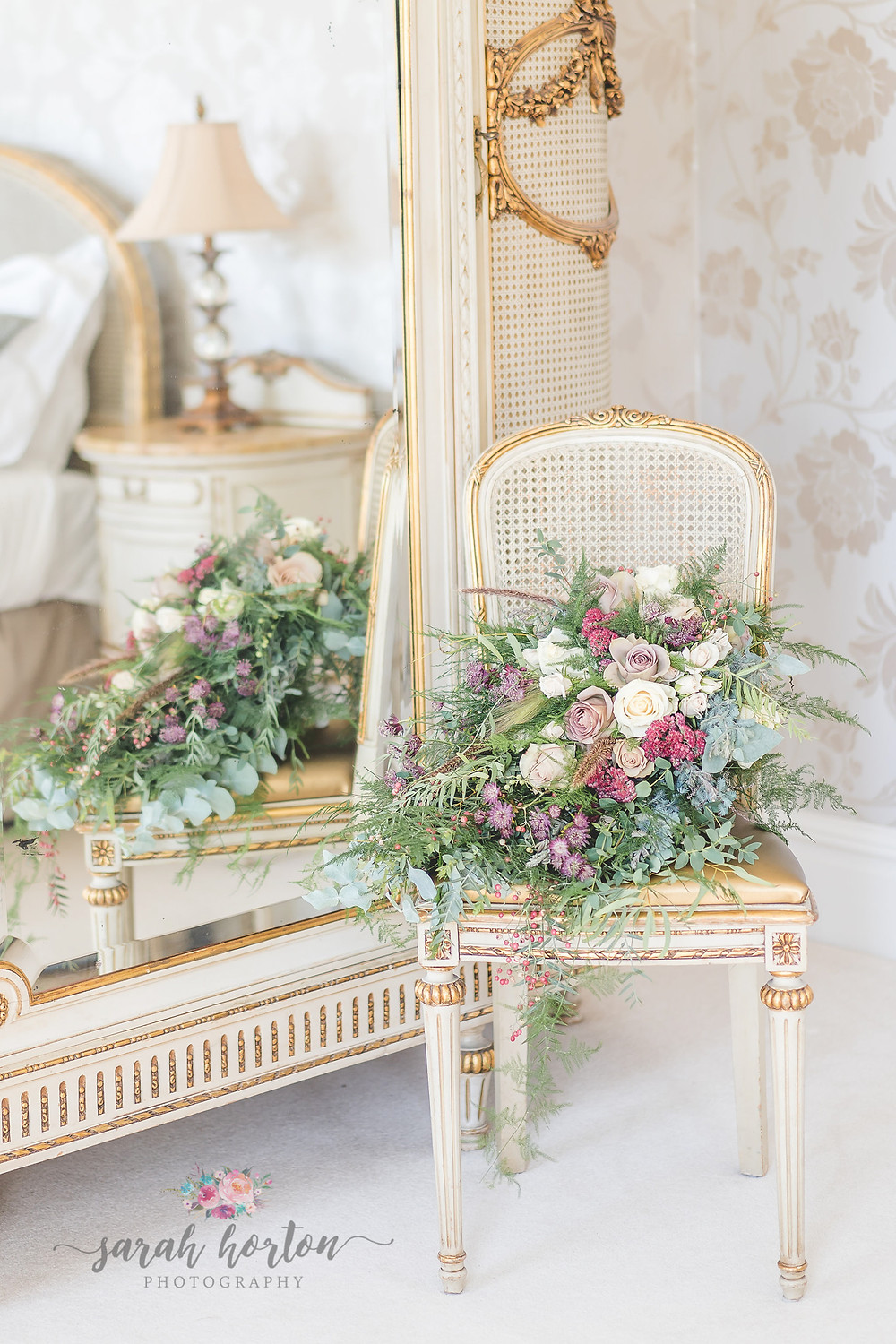 flowing bouquet surrounded by gold furniture in the Delamere Manor bridal suite