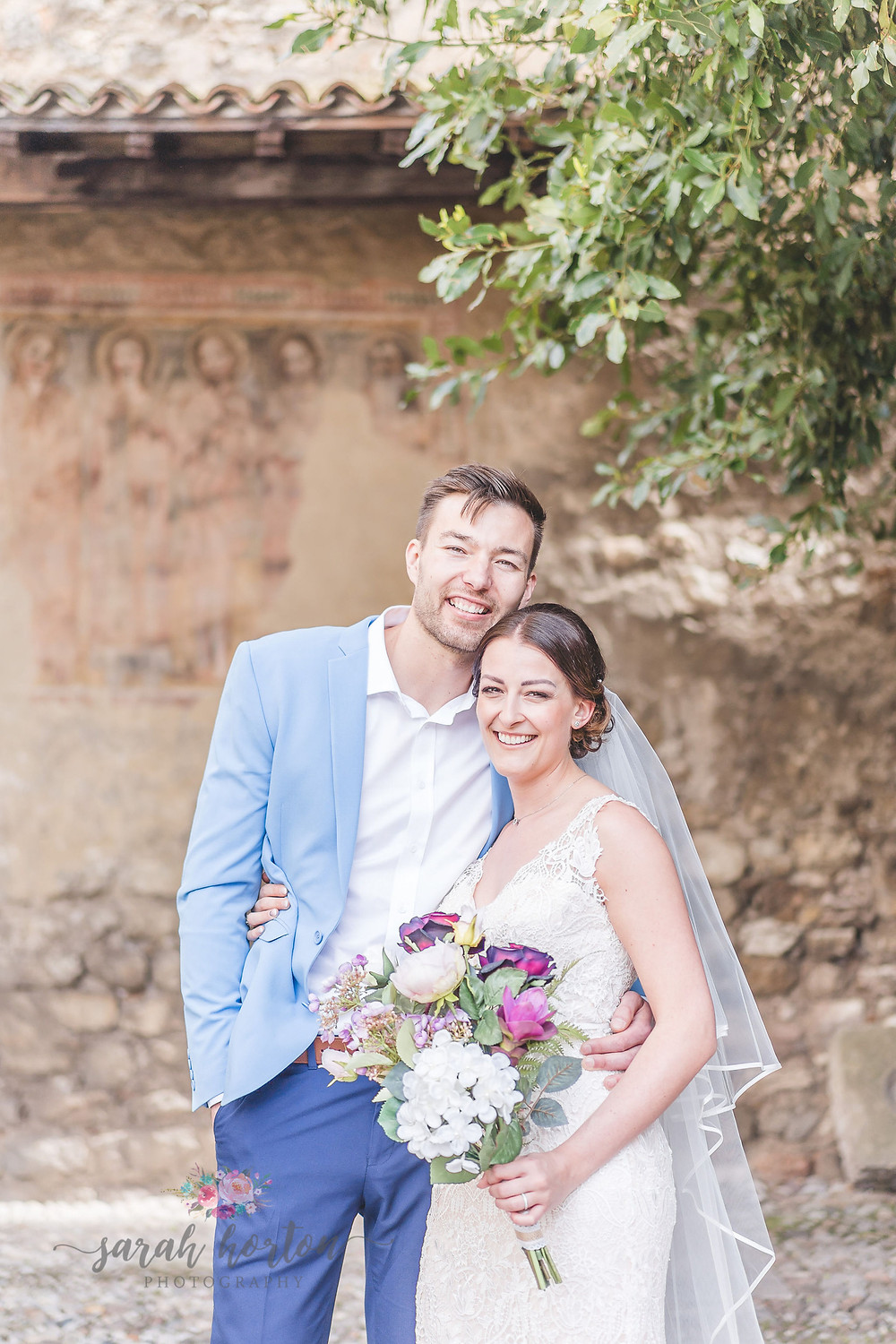 couple smile against Italian castle walls