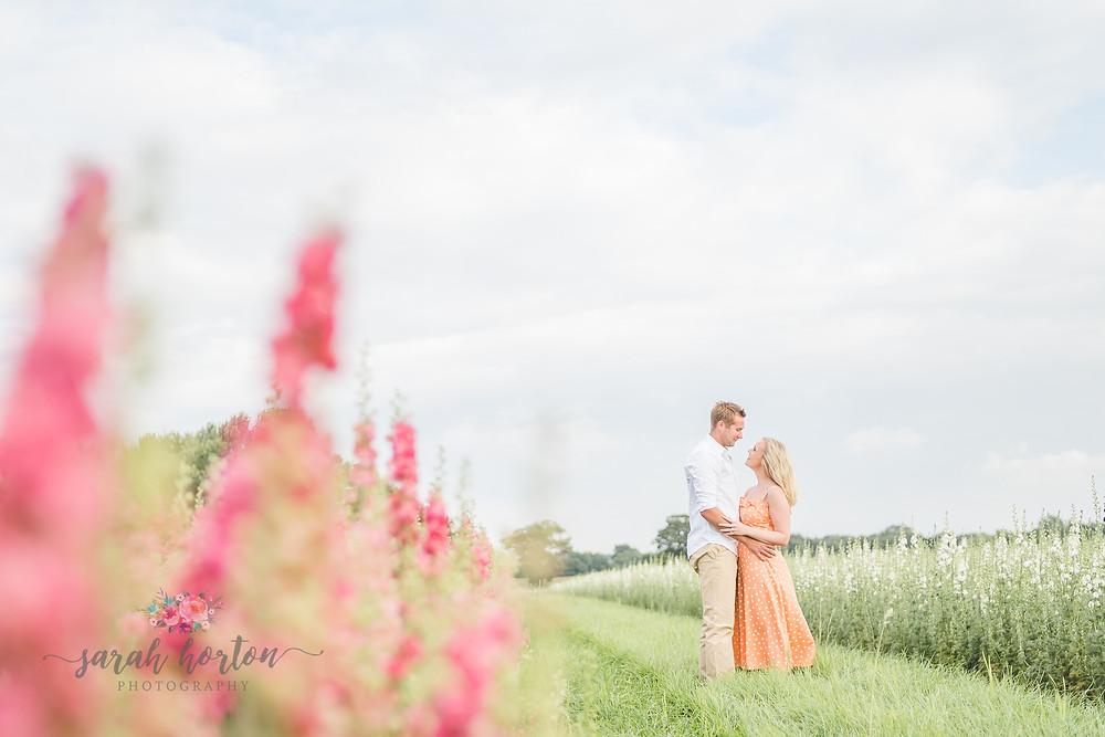 couple stood amongst delphiniums at Shropshire petals confetti fields