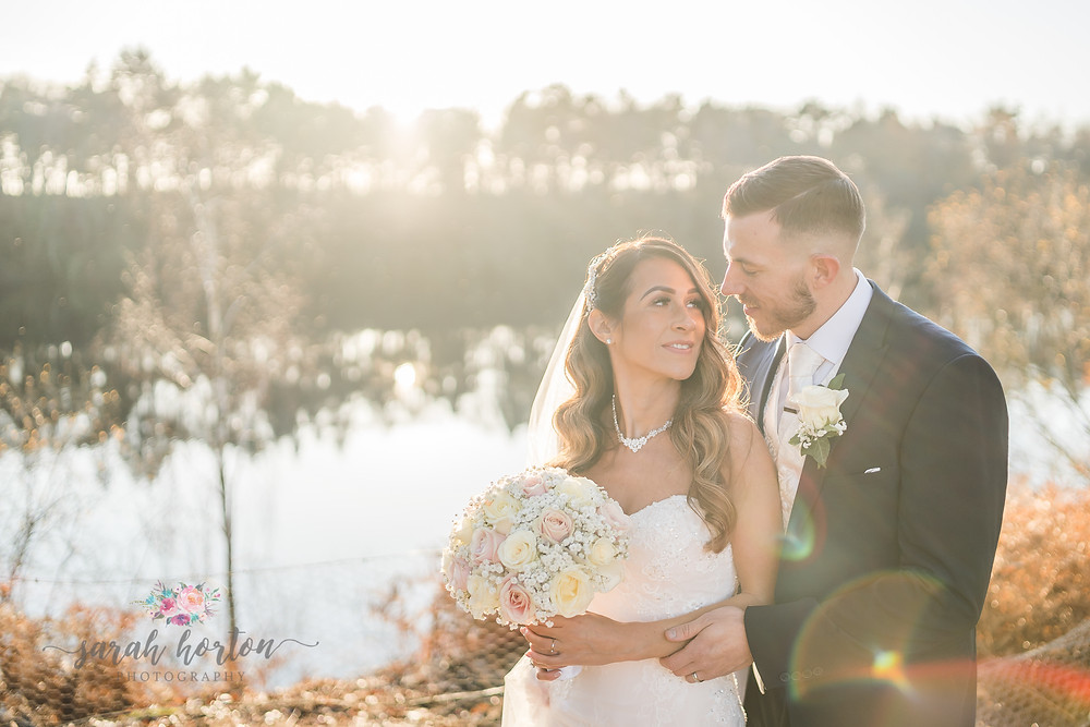 Bride and groom in the winter sun at nunsmere hall lake