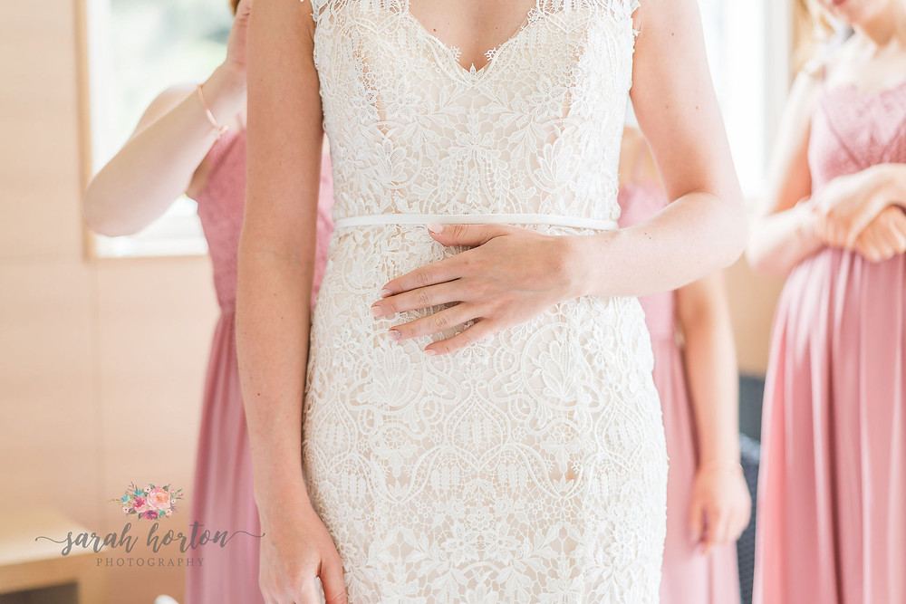 brides hand on lace wedding dress