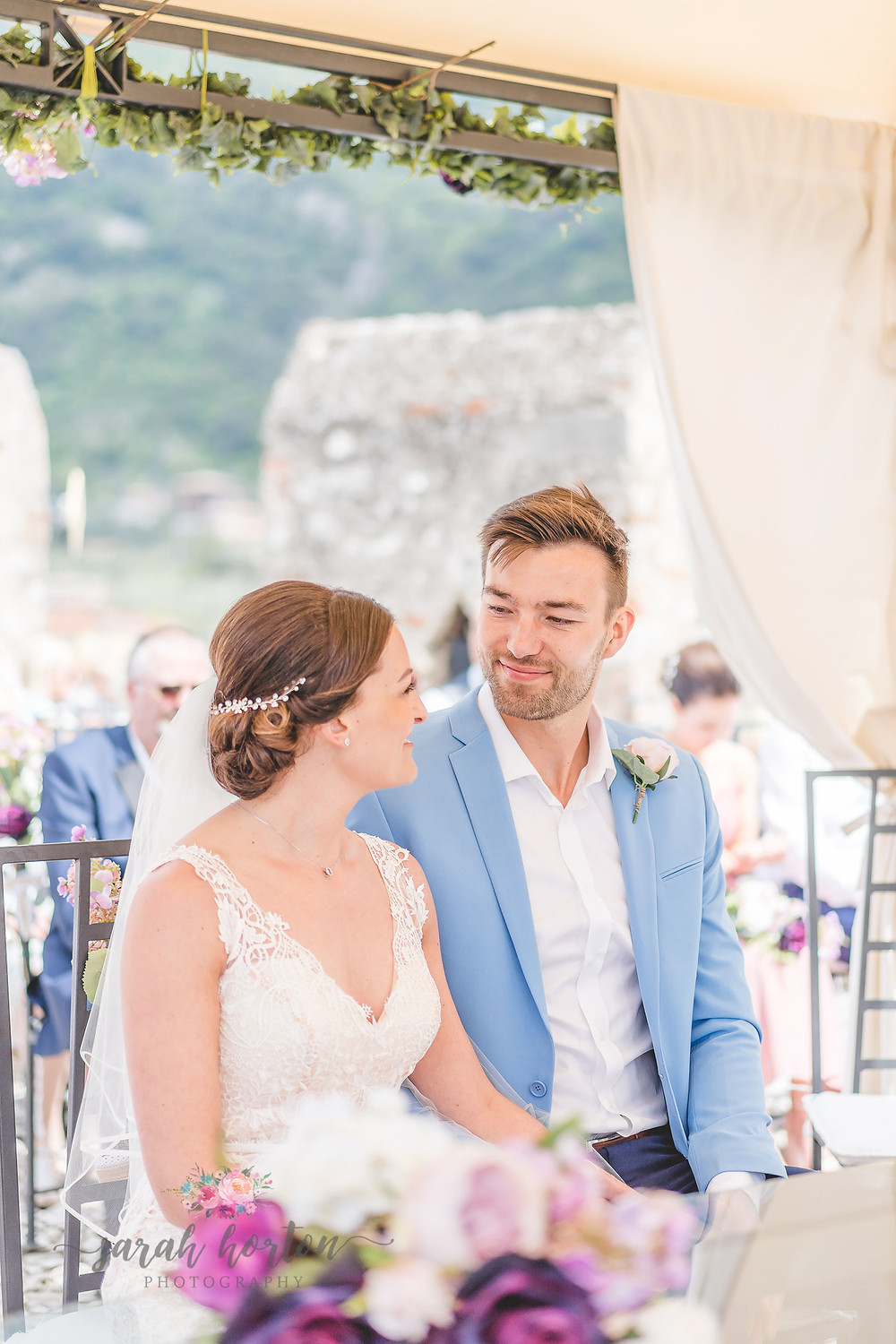 bride and groom are married under canopy at malcesine castle wedding