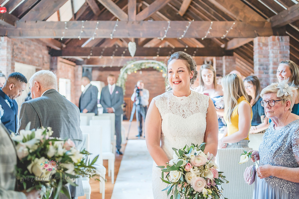 smiling bride walks aisle at abbey wood barn