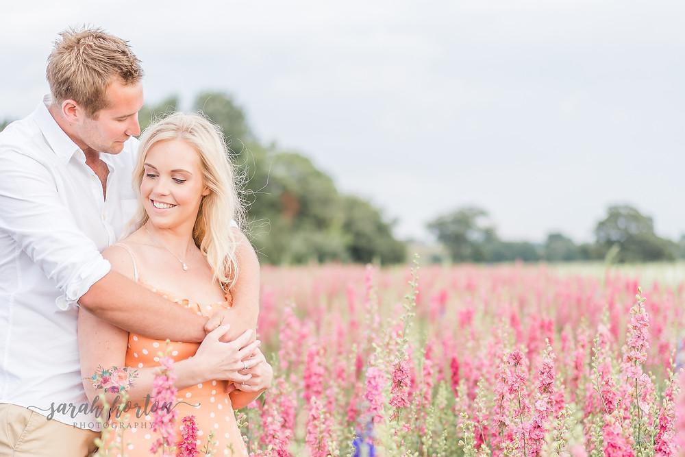 couple amongst pink delphiniums at Shropshire petals confetti fields