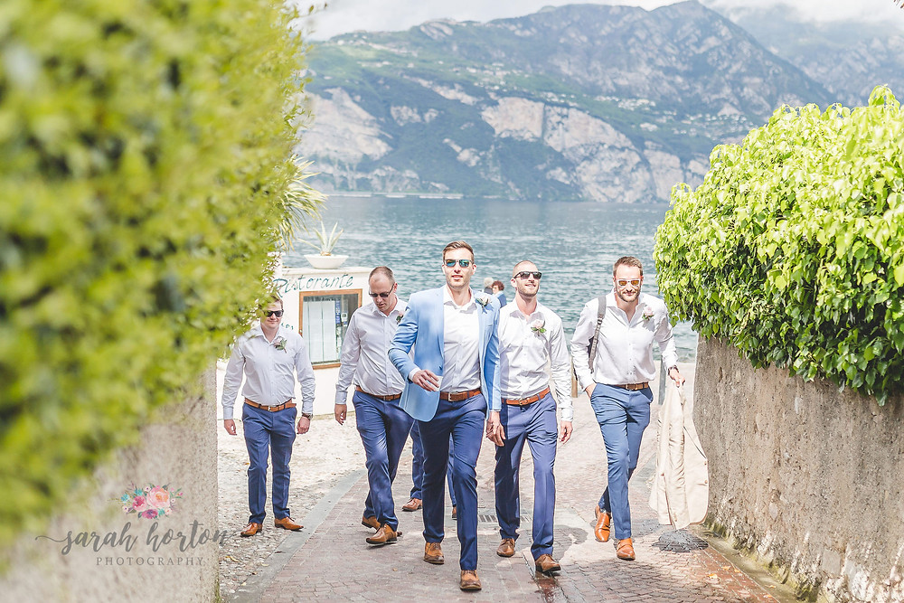 groomsmen walk up steep malcesine street