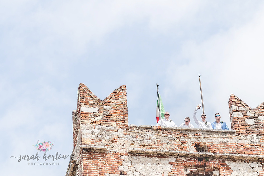 groom waves from the roof of malcesine castle wedding