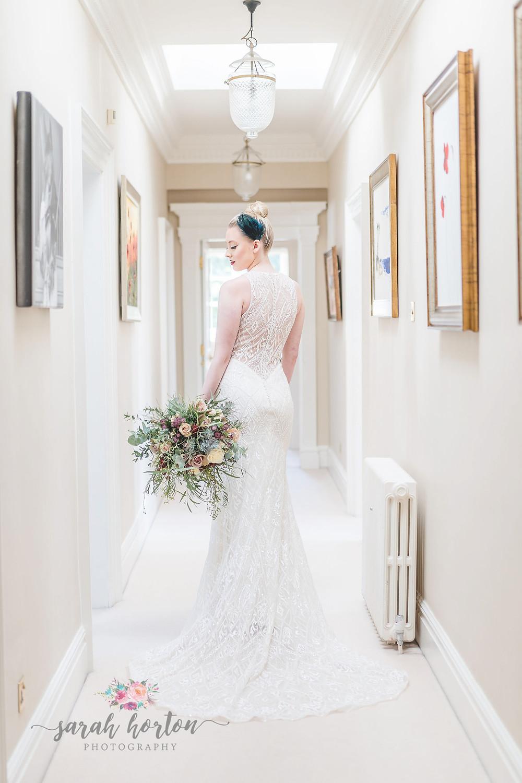 bride stands in light corridor at Delamere manor Cheshire venue