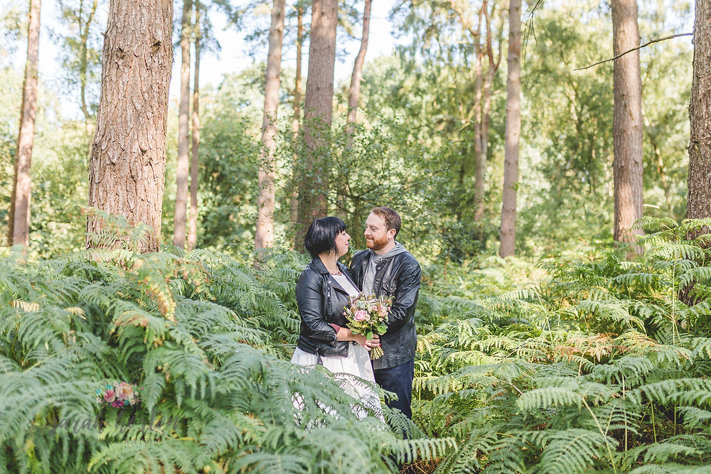 married couple in leather jackets in the forest