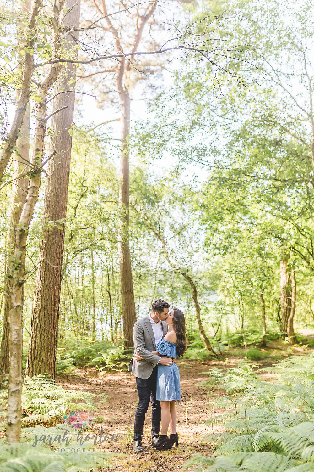 engaged couple kiss in the forest