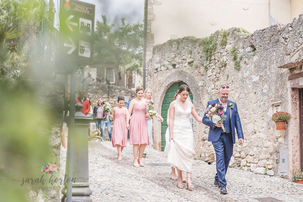 bride walks with dad through cobbled malcesine streets