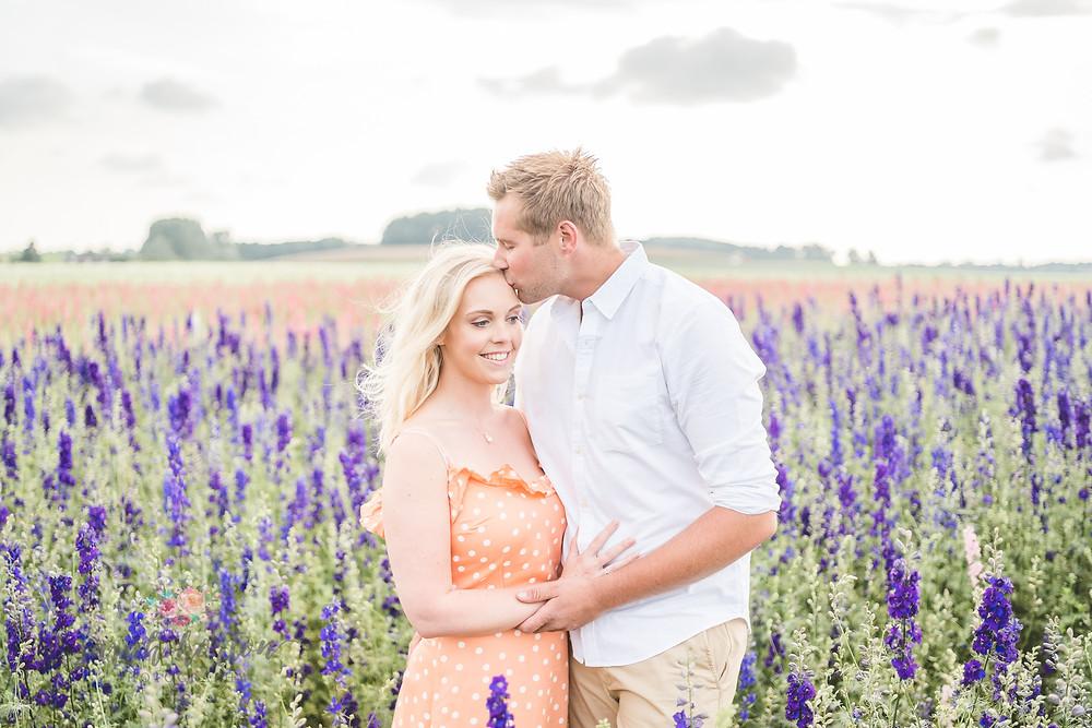 couple kiss amongst purple delphiniums at Shropshire petals confetti fields
