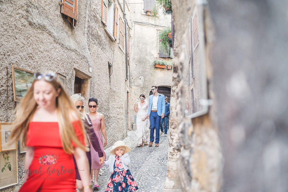 wedding party walk through malcesine streets with ice creams