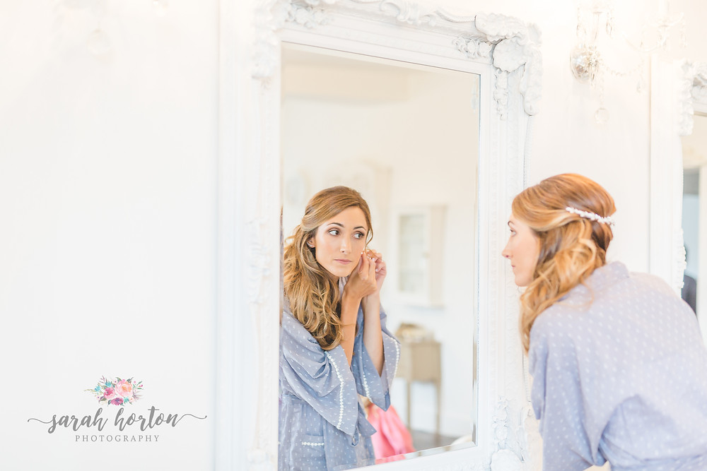 bride getting ready in mirror at alcumlow