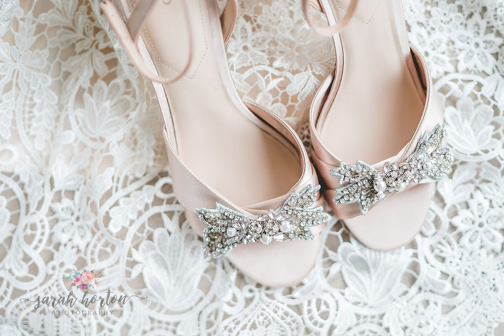 bridal shoes surrounded by lace wedding dress