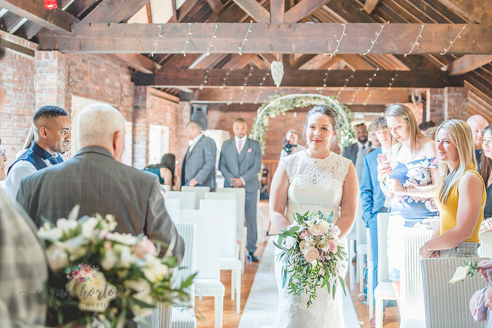 emotional bride walks down the aisle in Abbeywood barn