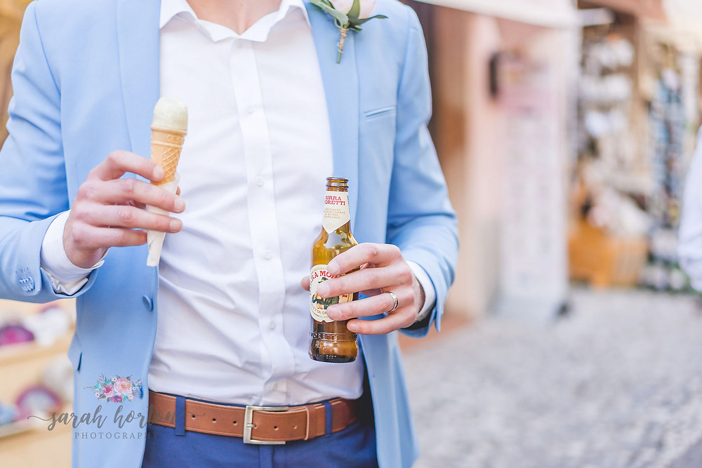 groom holds beer and ice cream