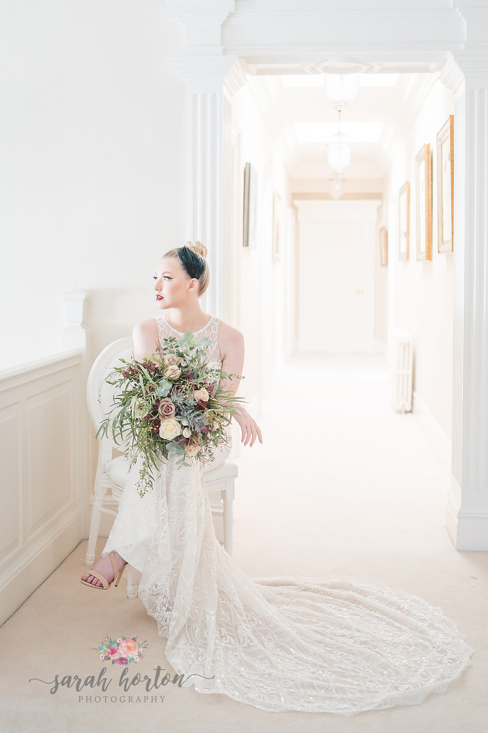 bride sitting on a chair in the light corridor at Cheshire wedding venue Delamere manor