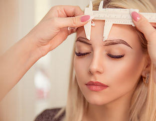 Changing the shape of the brows. Stylist measuring the eyebrows with the ruler. Micropigme